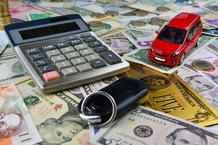 Calculator, keys and red toy car on a variety of national currency banknotes background. Between the banknotes there is one symbolic gold dollar banknote.  Concept of the cost of purchasing, renting and maintaining a car - image Stockfoto