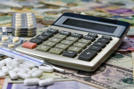 Calculator, pills and thermometer on the background of the various national currency banknotes. The concept of medical availability and increasing medical expenses - image Stockfoto