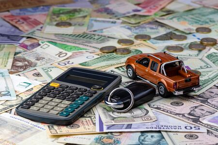 Calculator, keys and pickup toy car on a variety of national currency banknotes background.  Concept of the cost of purchasing, renting and maintaining a car - image Stockfoto
