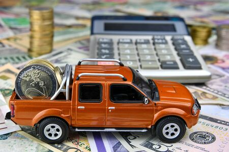 Calculator and pickup toy car with coins in the cargo box on a variety of national currency banknotes background.  Concept of the cost of purchasing, renting and maintaining a car - image