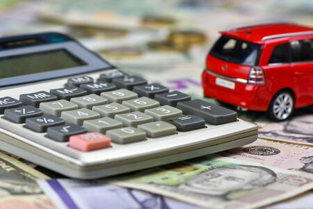 Calculator and red toy car on a variety of national currency banknotes background.  Concept of the cost of purchasing, renting and maintaining a car  - image