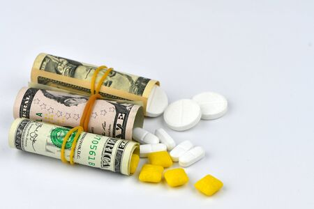 Dollar rolled up with pills flowing out isolated on white background, high costs of expensive medication concept. Copy space.