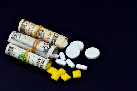 Dollar rolled up with pills flowing out isolated on black background, high costs of expensive medication concept. Copy space. 版權商用圖片