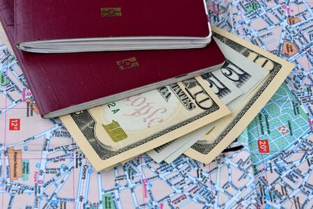 Two passports and a few dollars banknotes on a city map background. Tourism concept.
