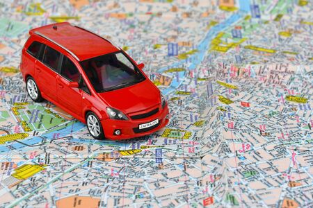 Close-up of a red car on a tourist map background. The concept of car tourism.