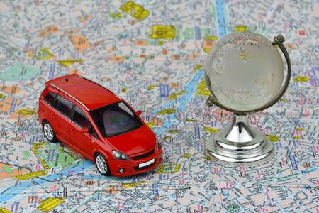 Close-up of a red car and a glass globe on a tourist map background. The concept of car tourism.