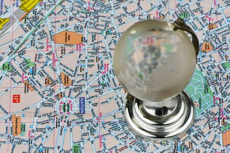 Close-up of a glass globe on a tourist map background. Selective focus on the map. The concept of  tourism.