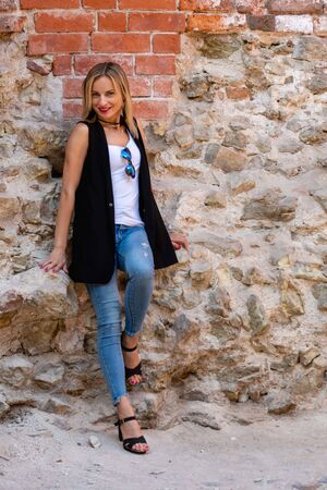 A beautiful woman  with long blond hair, a white blouse and blue jeaans  by the stone wall of the old town.