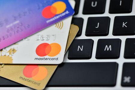 Three credit cards on a computer keyboard - image Фото со стока