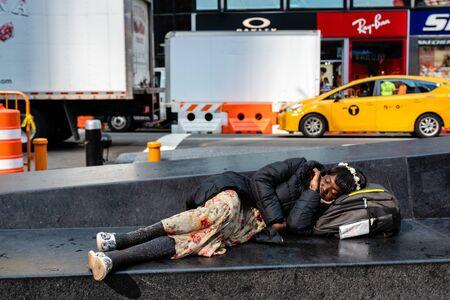 Nueva York, Estados Unidos - 6 de junio de 2019: mujer negra acostada en un banco de piedra en Nueva York, Time Square, Manhattan.