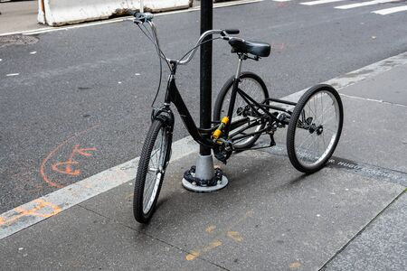 New York, USA - June 21, 2019: A black tricycle parked on the side of a street in Manhattan.