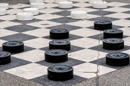 Large plastic checkers painted on the pavement cells in a city park