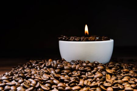 White coffee cup full of coffee beans and burning candle on top of coffee bean stack - image