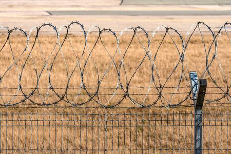 close-up of fence with barbed wire, security concept