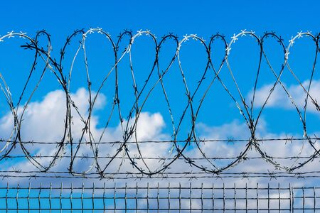 fence with barbed wire against blue sky with clouds, security concept