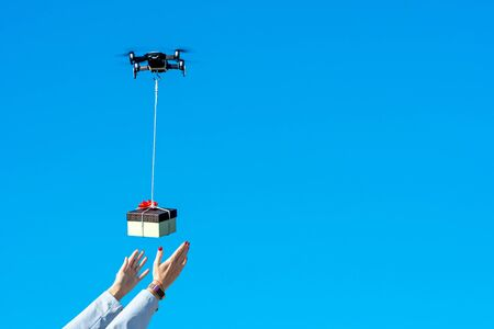 multicopter drone flying with a gift box isolated on a blue sky, concept of modern fast delivery method by using drones Stock Photo