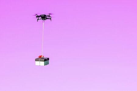 multicopter drone flying with a gift box isolated on a pink background, concept of modern fast delivery method by using drones