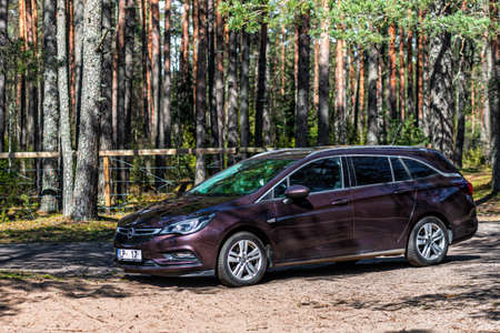 Galkalne, Latvia - April 22, 2020: brown shiny car Opel Astra Sport Tourer  parked in forest roadside on blurred bokeh background on bright sunny day, the concept of family recreation and transport solutions