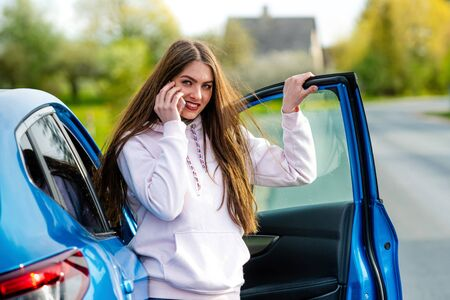 young beautiful emotional woman gets out of the car and talks on the phone