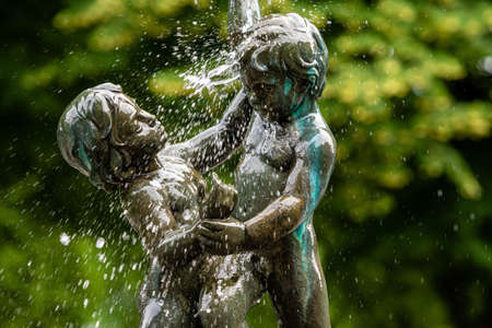 Riga, Latvia- July 3, 2020: fragment of the oldest Riga fountain SEASONS in Vermane Garden, sculptures of two boys in splashes of water on a defocused background Éditoriale