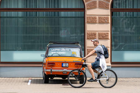 Riga, Latvia- July 3, 2020: a vintage car with advertising signs is parked in the parking lot to attract parking customers