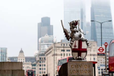 A dragon sculpture with the Coat of Arms of the City of London at the London Bridge. Blurred skyscrapers and red double decker buses in the background - image