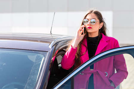 young beautiful emotional businesswoman gets out of the car and talks on the phone