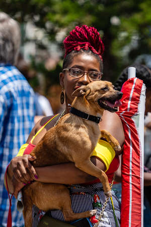 New York, USA - June 22, 2019: an African woman with a dog in her hand walks in the crowd on the street 新闻类图片