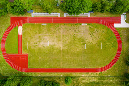aerial view of empty green football field and red running tracks, race track in a opened stadium.
