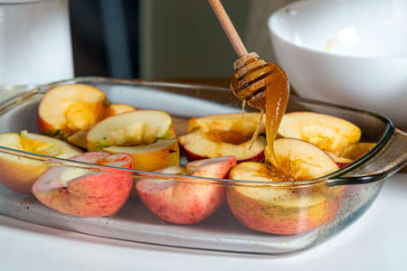 female hands with stick pouring apples with honey in a glass container and prepare them for cooking, homemade desert concept