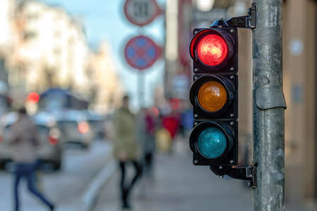 close-up of small traffic semaphore with red light against the backdro of the city traffic Foto de archivo