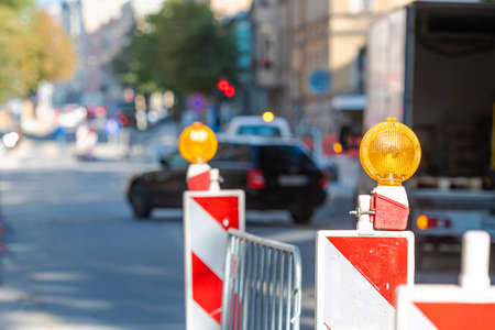 warning poles with orange light signal on the road about repairs work, blurred street with cars on background