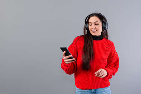 positive teenager brunette in red sweater listens to music on smartphone in headphones, isolated on gray Фото со стока