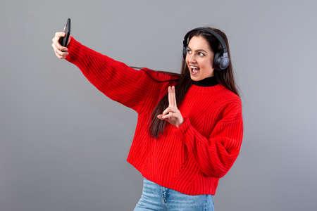 positive teen brunette with headphones dressed in a red sweater takes a selfie with a smartphone, isolated on gray Фото со стока