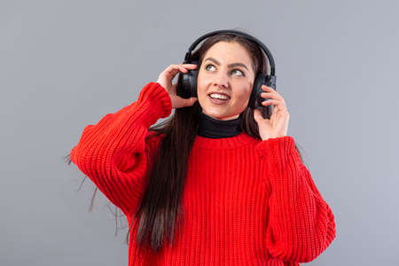 positive teenager woman dressed in red sweater listens to music on headphones, isolated on gray