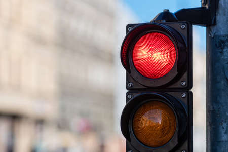 closeup of traffic semaphore with red light on defocused city street background with copy space