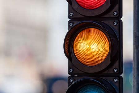 closeup of traffic semaphore with orange light on defocused city street background with copy space Archivio Fotografico