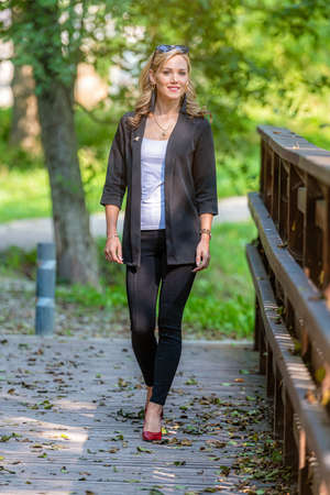 young positive, smiling, legant woman walks on a wooden footbridge on a sunny autumn day Stock Photo