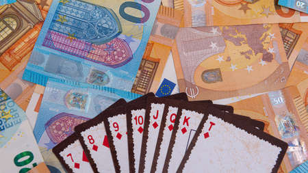 playing cards against the background of euro banknotes, gambling concept, close-up