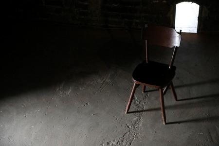 Wooden chair in a dark old room Stock fotó