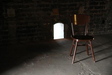 Wooden chair in a dark old room Archivio Fotografico