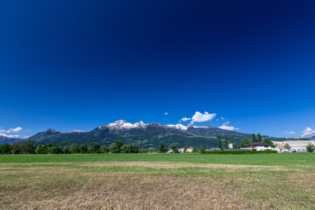 View of the green field and mountains of the Alps in Liechtenstein. Beautiful landscape
