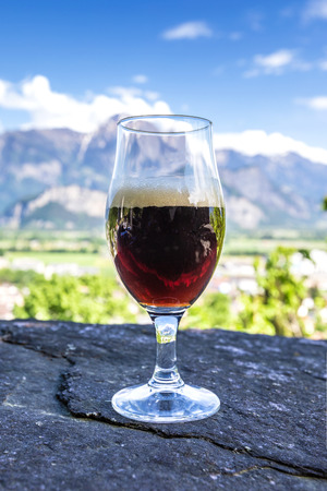 A glass of fresh beer on the background of the mountains. Alps landscape