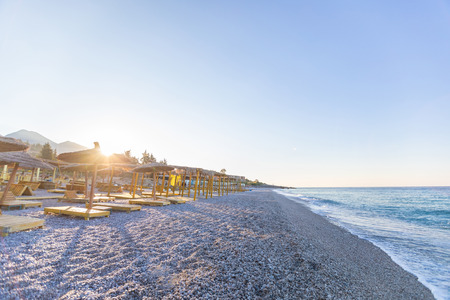 Sunrise over an empty beach with umbrellas. Albania