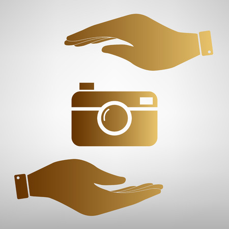 whim of fashion: Digital photo camera icon. Save or protect symbol by hands. Golden Effect.
