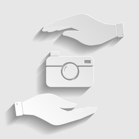 whim of fashion: Digital photo camera icon. Save or protect symbol by hands. Paper style icon with shadow on gray.