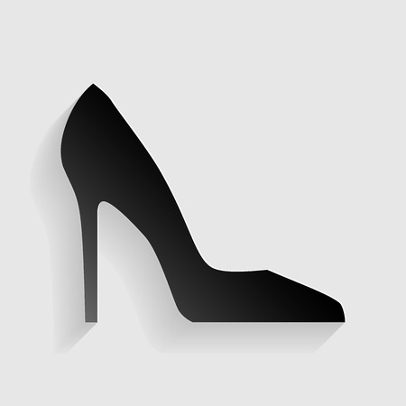 woman shadow: Woman shoe sign. Black paper with shadow on gray background.