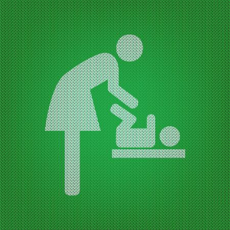Symbol for women and baby, baby changing. white icon on the green knitwear or woolen cloth texture.
