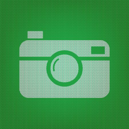 Digital photo camera sign. white icon on the green knitwear or woolen cloth texture. Illustration