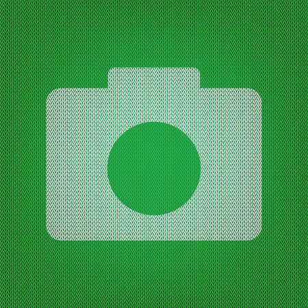 Digital camera sign. white icon on the green knitwear or woolen cloth texture.